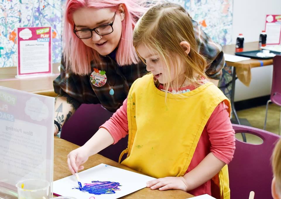 Staff Member Helping Little Girl With Messy Art