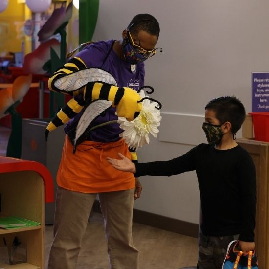 Port Discovery staff member and bee puppet talk to boy