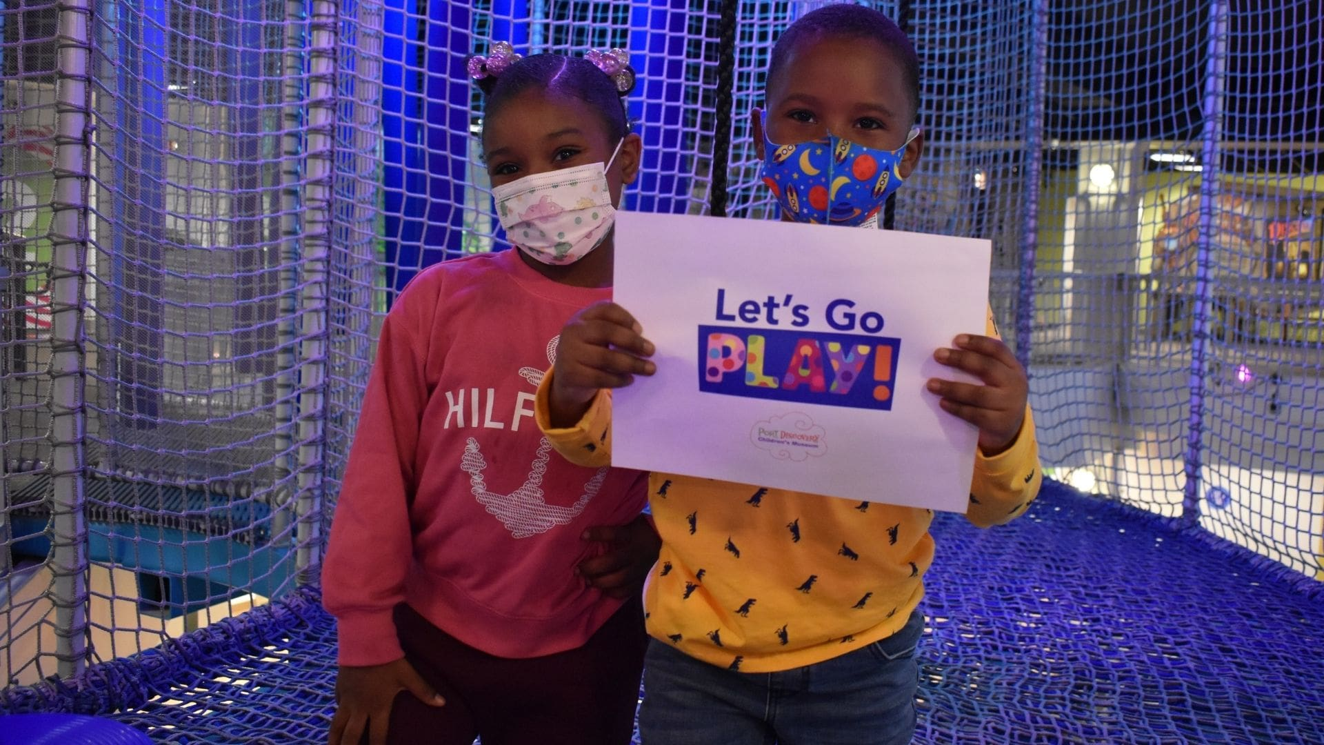 Two children holding sign that says Lets Play