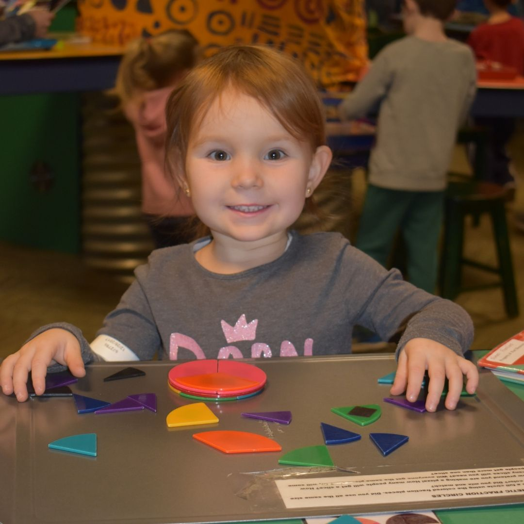 Child working on puzzle inside Oasis exhibit