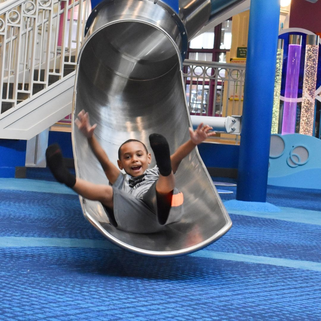 Little Boy Smiling at end of Slide
